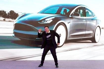 Elon Musk, CEO de Tesla, baila junto a uno de los vehículos de la marca en una exposición Shanghai, China, en enero de 2020. (REUTERS/Aly Song/File Photo)