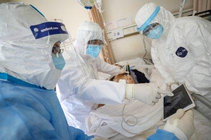 Trabajadores médicos en trajes protectores atienden a un paciente dentro de un pabellón aislado del Hospital de la Cruz Roja de Wuhan, el 16 de febrero de 2020 (China Daily via REUTERS)