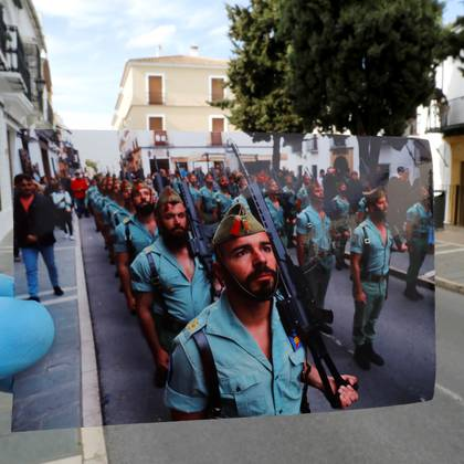 A Reuters photographer holds a picture of Spanish legionnaires marching before a procession taken in April, 2019, in front of the street of the procession, on Palm Sunday, the first day of Holy Week, amid the coronavirus disease (COVID-19) outbreak, in Ronda, southern Spain, April 5, 2020. Picture taken April 5, 2020. REUTERS/Jon Nazca/Illustration