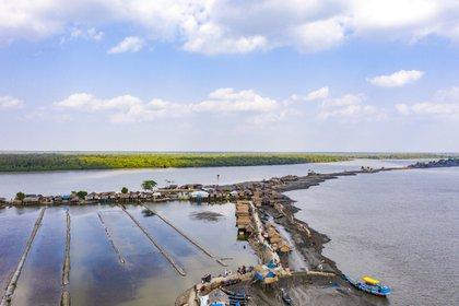 La aldea de Kalabogi se encuentra en el lado norte del delta Sundarbans de Bangladesh. La aldea ahora consta de dos filas de casas de plataformas gubernamentales, ya que los edificios originales fueron arrastrados por el agua. Dos tercios de Bangladesh se encuentran a menos de cinco metros sobre el nivel del mar.