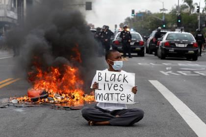 Un manifestante sostiene una pancarta, en Los Ángeles, California, EEUU, el 30 de mayo,  2020. REUTERS/Patrick T. Fallon