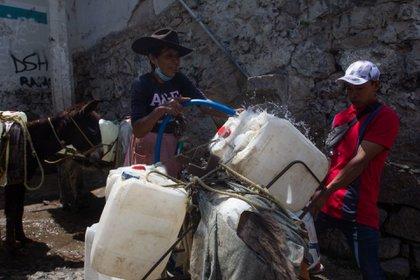 CIUDAD DE MÉXICO, 07ABRIL2021 - La señora Aurelia Martínez llena de agua los bidones que cargan sus burros en el pueblo de Santa Cruz Acalpixca, Xochimilco  Foto: Graciela López / Cuartoscuro.com