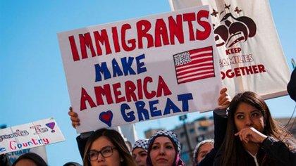 """Una mujer sostiene un cartel que dice: """"Los inmigrantes hacen grande a Estados Unidos"""", Durante un mitin"""