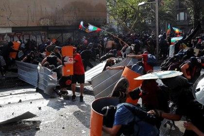 Enfrentamientos entre la policía y los manifestantes, que portan la bandera mapuche (Reuters)