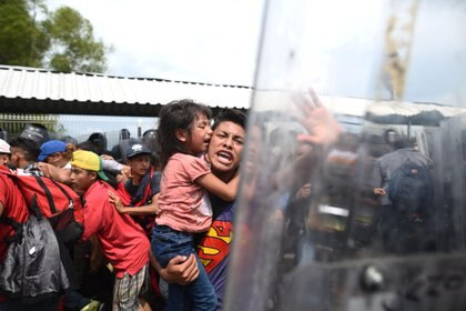 Un migrante hondureño con una menor en brazos grita hacia los miembros de la policía mexicana en el paso fronterizo entre Guatemala y México. (EFE/Edwin Bercían)