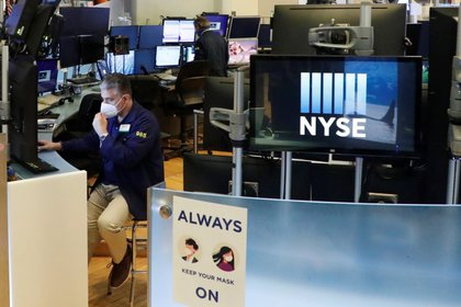 Un operador se ajusta la máscara mientras trabaja en el piso de la Bolsa de Nueva York, EEUU, 28 mayo 2020. (REUTERS/Lucas Jackson)