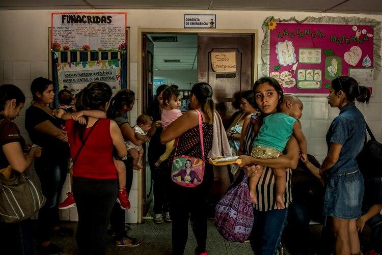 Las madres esperan durante horas a que sus hijos sean admitidos en la sala de emergencias en el ala pediátrica del Hospital Central. Credit (Meridith Kohut/The New York Times)