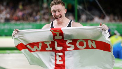 "FILE PHOTO: ON THIS DAY -- April 7  April 7, 2018     GYMNASTICS - England's Nile Wilson celebrates winning his second Commonwealth Games gold medal in the men's individual all-around gymnastics final in Gold Coast, Australia.     England had earlier won the men's team event and Wilson posted a score of 15.100 with a near-faultless display on the horizontal bar in the final rotation of the all-around individual finals to steal victory.     ""It was a battle on the high bar,"" said Wilson, who was nursing a wrist injury. ""You can't write it, to finish the way it did."" REUTERS/Athit Perawongmetha/File Photo"