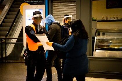 Una mujer le presenta su autorización para circular a un policía en la estación Constitución