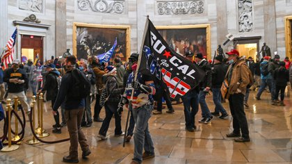Seguidores de Trump vagan bajo la Rotonda del Capitolio después de invadir el edificio (Foto de Saul LOEB / AFP)