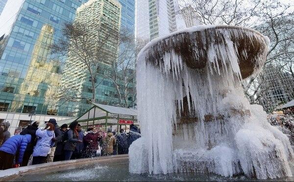 Ciudadanos y turistas posan junto a una fuente congelada en Nueva York (AP)