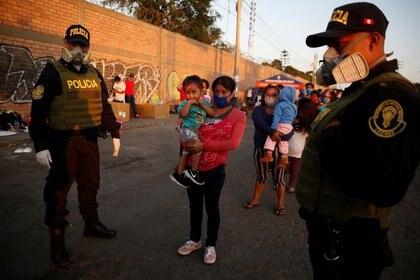 Personas fuera de una base de la Fuerza Aérea peruana espernado por vuelos que los lleven de regreso al la amazonía local en medio de la propagación del coronavirus, en Lima, Perú, el 24 de abril (REUTERS/Sebastián Castañeda)