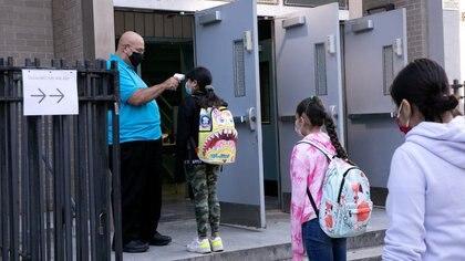 Foto del jueves de un grupo de niños haciendo fila para que les tomen la temperatura antes de ingresar a una escuela en Brooklyn, Nueva York.  Oct 1, 2020. REUTERS/Caitlin Ochs