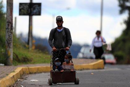 Un ciudadano venezolano y dos niños caminan por la carretera, de regreso a Venezuela (EFE/ José Jácome)
