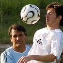Argentina's Lionel Messi (R) chests the ball while being watched by coach assistant Hugo Tocalli during a soccer practice session in Herzogenaurach June 25, 2006 ahead of their next World Cup match against Germany. REUTERS/Enrique Marcarian (GERMANY)