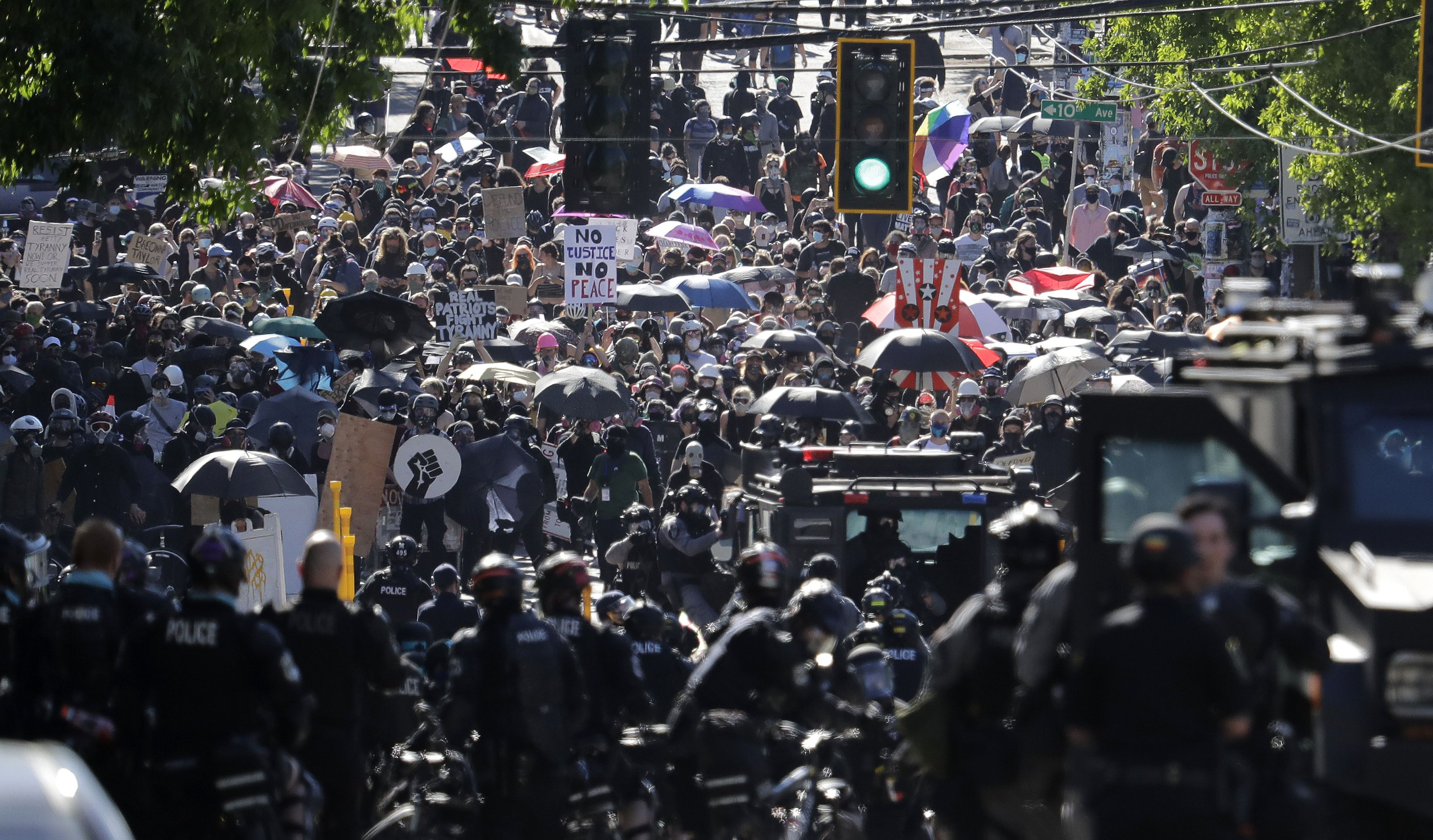 Police clash with protesters Saturday, July 25, 2020, during a Black Lives Matter protest near the Seattle Police East Precinct headquarters in Seattle. A large group of protesters were marching Saturday in Seattle in support of Black Lives Matter and against police brutality and racial injustice. (AP Photo/Ted S. Warren)
