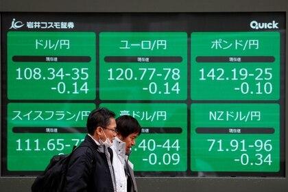 Imagen de archivo de peatones pasando frente a una pantalla electrónica con la cotización del yen frente a monedas mundiales en Tokio, Japón. 8 enero 2020. REUTERS/Issei Kato