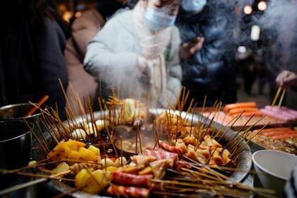 Snacks locales en el mercado callejero, un año después de la irrupción del virus SARS-CoV-2 en Wuhan, provincia china de Hubei (REUTERS/Aly Song)