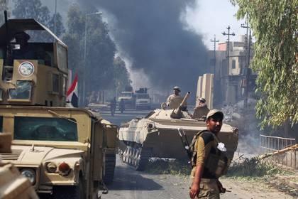 Vehículos blindados del ejército con columnas de humo en el fondo (AFP)