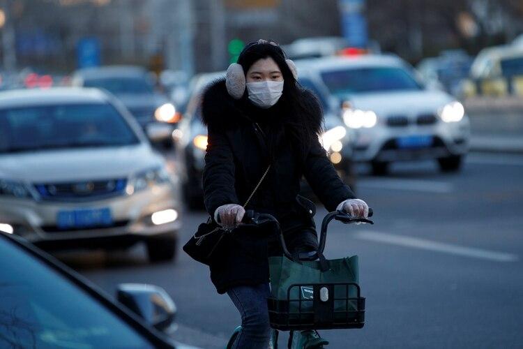 Una mujer abrigada y protegida con una mascarilla en Beijing (Reuters)