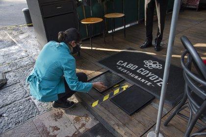 Alfombras sanitizantes en la entrada de un restaurante (Photo by CLAUDIO CRUZ / AFP)