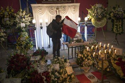 Un joven coloca una bandera sobre el ataúd de Inti Sotelo Camargo en su velorio en Lima (AP Photo/Rodrigo Abd)