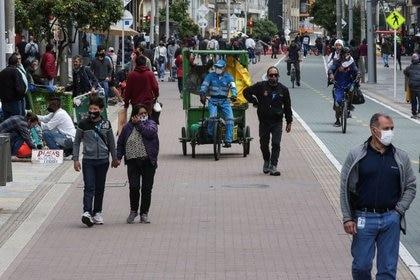 Personas con máscaras faciales caminan por una calle céntrica de Bogotá.