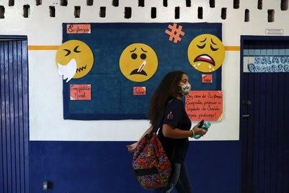 Un estudiante pasa junto a un panel de información sobre los síntomas de la enfermedad por coronavirus en el primer día de clases de las escuelas del estado de Sao Paulo, en la escuela Professor Milton da Silva Rodrigues en Sao Paulo, Brasil, 3 de noviembre de 2020.  3 nov 2020. REUTERS/Amanda Perobelli