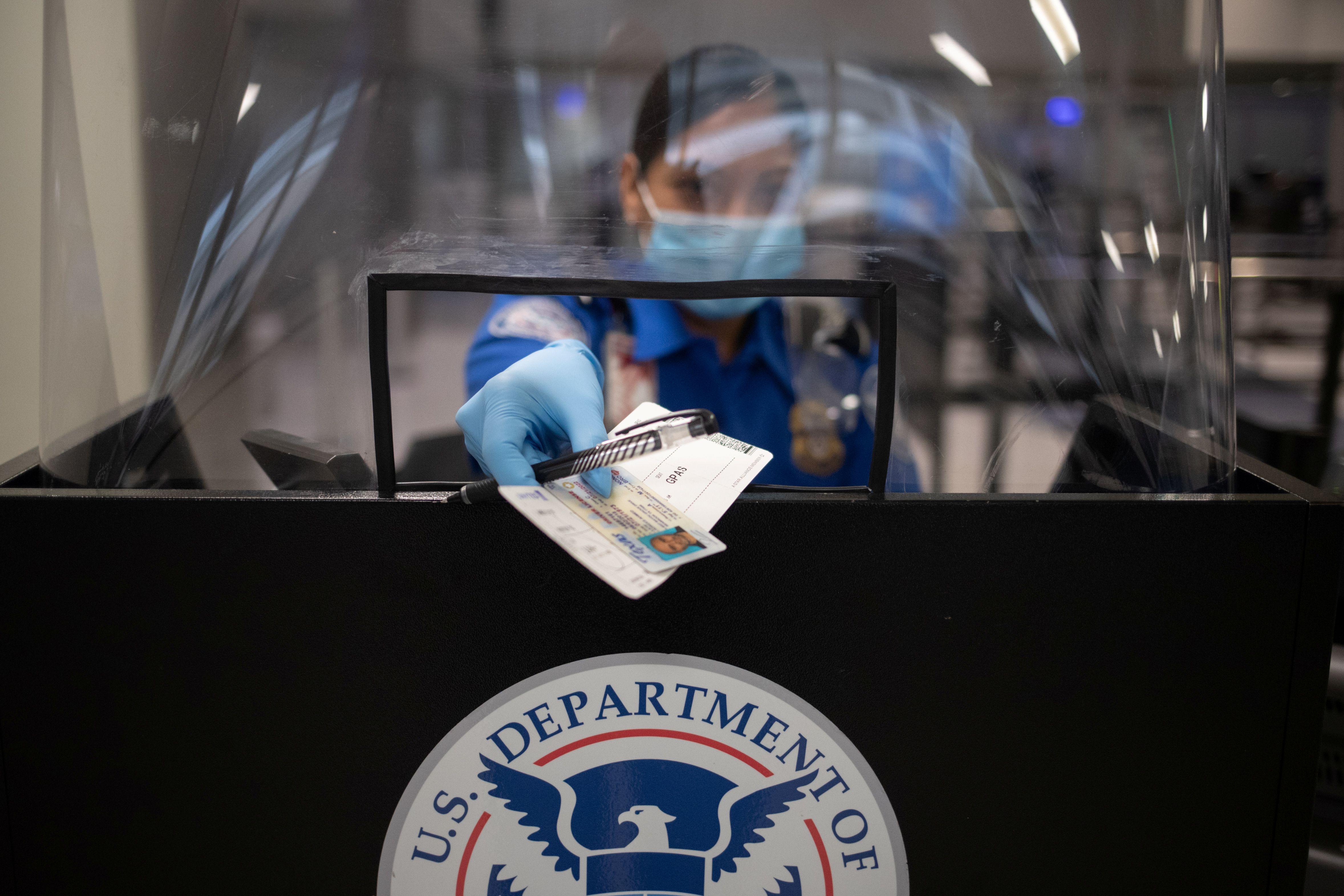 Una empleada de la TSA devuelve los documentos a un pasajero, ahora con barbijo y cobertor plástico producto del coronavirus. REUTERS/Adrees Latif