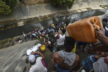 Venezolanos recogen agua de un canal de aguas servidas en el río Guaire, en Caracas, en medio de un gran corte de luz. En el país de las reinas de la belleza hoy un producto de aseo puede tener el valor de medio salario de una empleada. (JUAN BARRETO / AFP)