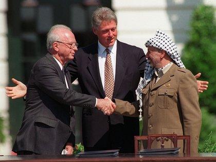 El Primer Ministro de Israel Yitzhak Rabin y el lider de la OLP Yasser Arafat se dan la mano bajo la mirada de Bill Clinton, en la ceremonia de la firma de los acuerdos de Oslo el 13 de septiembre de 1993, en Washington (AP Photo/Ron Edmonds)