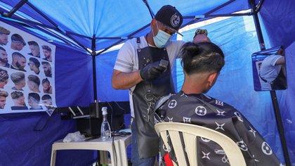 Un venezolano corta el cabello a un hombre en su puesto parte de una feria ambulante (EFE/Martin Alipaz)