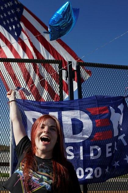 Una seguidora del candidato demócrata Joe Biden flamea una bandera en Wilmington, Delaware, Estados Unidos.  REUTERS/Kevin Lamarque