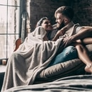 Beautiful young couple covered with blanket smiling and looking at each other while sitting in an armchair at home together