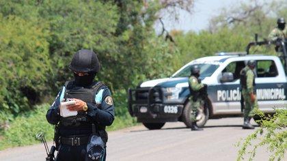 Policías prestan guardia en la zona donde un vehículo policial fue atacado por grupos armados, en Guanajuato (México). EFE/ STR/Archivo
