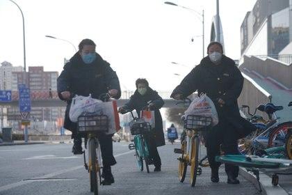 Mujeres en sus bicicletas con mascarillas contra el coronavirus en Beijing, China. REUTERS/Stringer