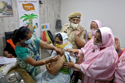 A woman is vaccinated with COVID-19 in India