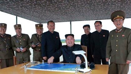 Un sonriente Kim Jong Un junto con sus generales luego del lanzamiento exitoso del misil Hwasong-12 (KNCA/AFP)