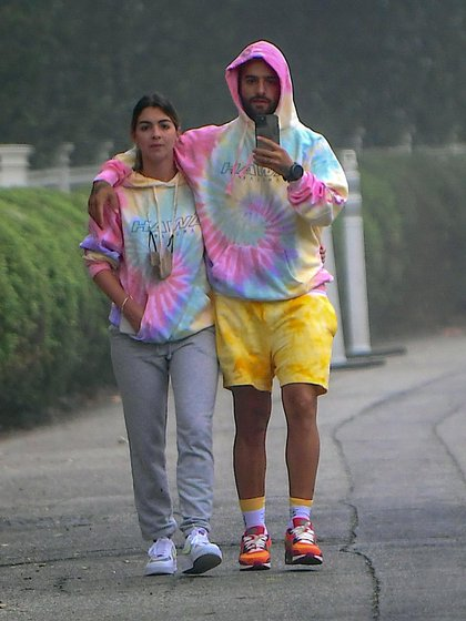 """Photo © 2020 Splash News/The Grosby Group  PREMIUM EXCLUSIVE  191020  Colombian Superstar, Maluma, was spotted out in Beverly Hills on Sunday morning, enjoyed a loved up stroll with rumored new girlfriend, Susana Gomez. The couple walked arm in arm while wearing matching Maluma """"Hawai"""" Tie Dye Hoodies. They put their arms around each other while taking a cute selfie one their way to breakfast.  Pictured: Maluma,Susana Gomez"""