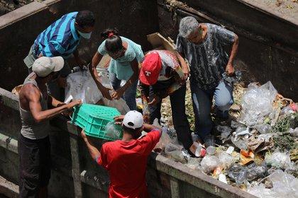 Personas buscando entre la basura en el mercado de Coche, en Caracas (REUTERS/Manaure Quintero)