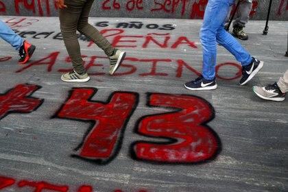 """Estudiantes de la Escuela Normal Rural de Ayotzinapa pasan frente a un letrero """"+43"""" pintado en el suelo durante una protesta frente a la Fiscalía General, antes del sexto aniversario de la desaparición de 43 estudiantes de la facultad, en la Ciudad de México, México el 25 de septiembre de 2020."""