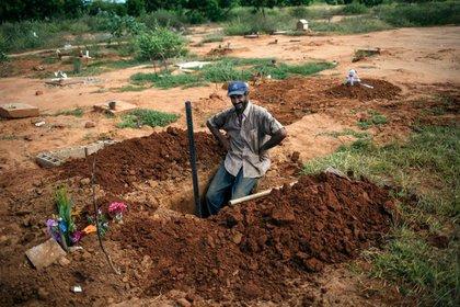 Un trabajador del cementerio posa para una fotografía mientras realiza sus tareas (AP)