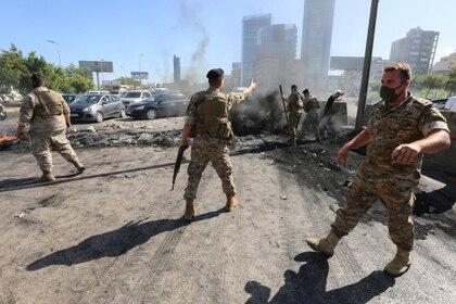 Soldados del ejército libanés abren una carretera que fue bloqueada por manifestantes durante una protesta provocada por la rápida caída de la libra y las crecientes dificultades económicas, el 12 de junio de 2020 (REUTERS/Aziz Taher)