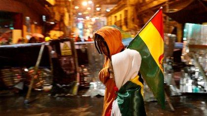 Un manifestante camina frente a una barricada en La Paz (Reuters)