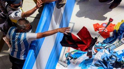 Un hincha arroja una rosa y una camiseta de Newell's al féretro de Maradona (Presidencia)
