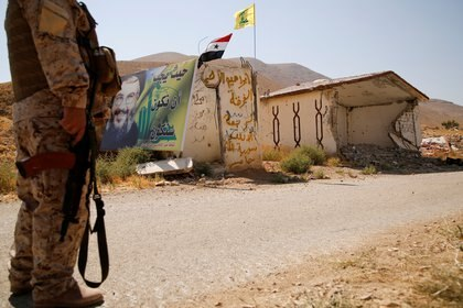 FILE PHOTO: A Hezbollah fighter stands as he holds his weapon in Western Qalamoun, Syria August 23, 2017. REUTERS/Omar Sanadiki/File Photo
