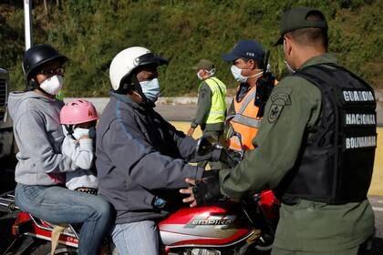 Personas en una motocicleta y usando mascarillas son revisadas por un efectivo de la Guardia Nacional Bolivariana en un punto de control después del inicio de la cuarentena en respuesta a la propagación del coronavirus, en Caracas, Venezuela, Marzo 16, 2020. REUTERS/Manaure Quintero
