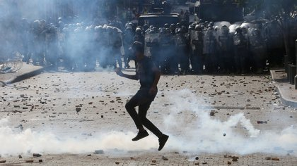A demonstrator hurls stones at riot police during a protest, following Tuesday's blast, in Beirut, Lebanon August 8, 2020. REUTERS/Aziz Taher
