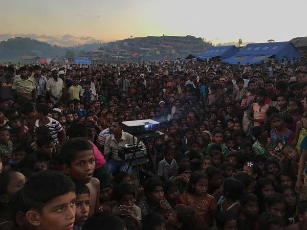 """El ganador absoluto como""""Fotógrafo del año"""" fue Jashim Salam (Bangladesh) con la foto """"Displaced"""" (Desplazado). La imagen fue capturada en Ukhia Bangladesh. Muestra a niños viendo una película que busca crear consciencia sobre el cuidado de la salud y cuestiones de sanidad."""