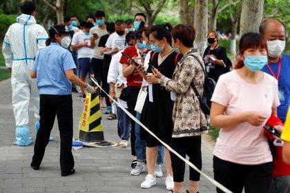 Personas hacen fila usando mascarillas en China